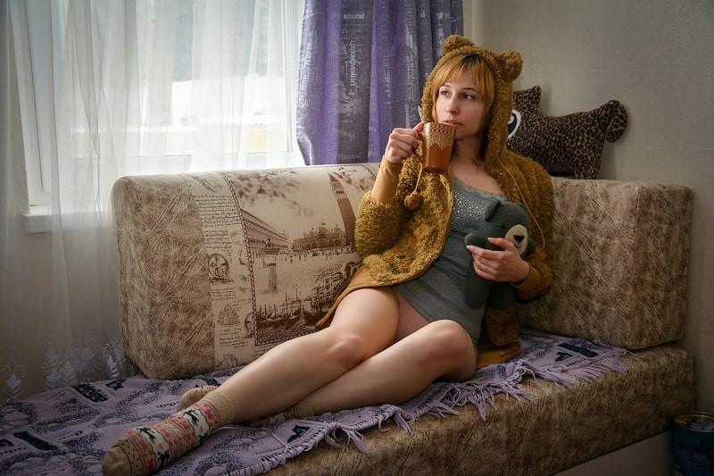 Девушка на диване в кофте пьет чай