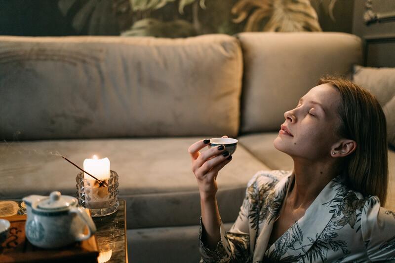 Девушка пьет чай со свечами