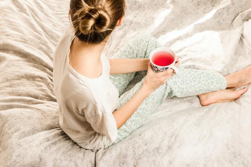 Девушка сидит с чаем на постели