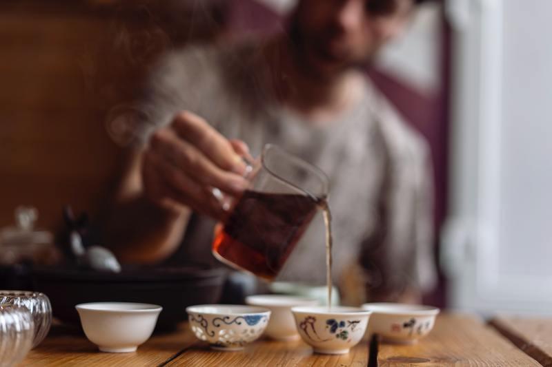 Мужчина разливает чай