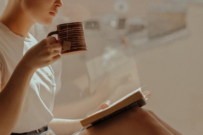 Девушка с книгой пьет чай