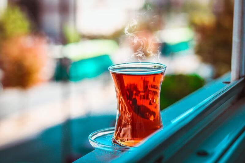 Узкий стакан чая на окне