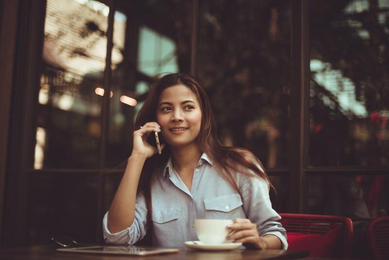 Девушка с телефоном пьет чай