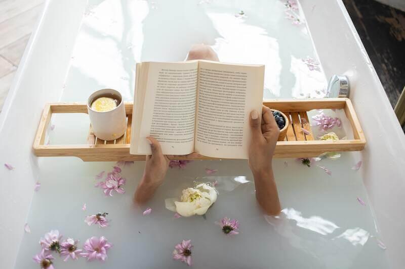 Девушка в ванной читает книгу