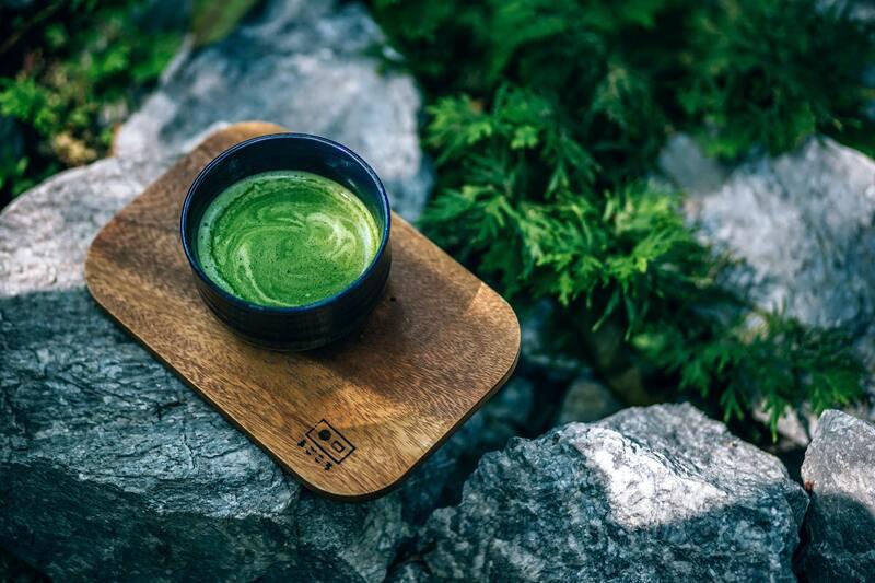 Чашка зеленого чая с молоком на камне