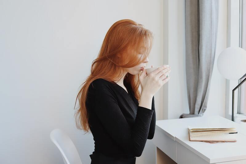 Рыжеволосая девушка в черном пьет чай