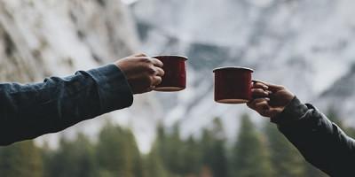 Две кружки в руках на фоне гор