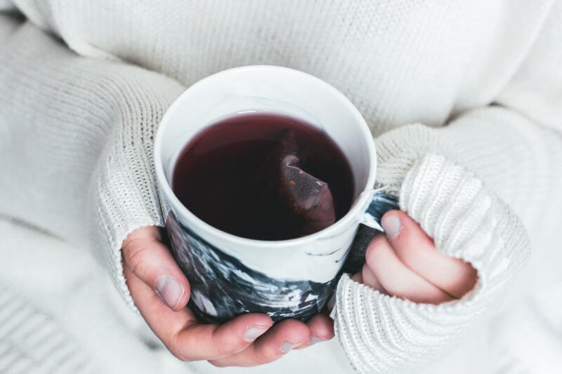 Девушка держит кружку чая