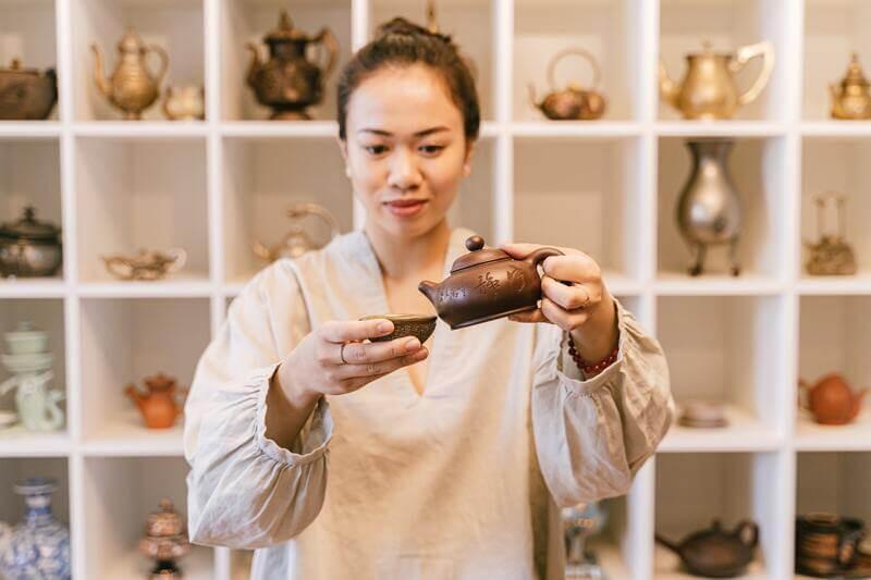 Девушка азиатка наливает чай