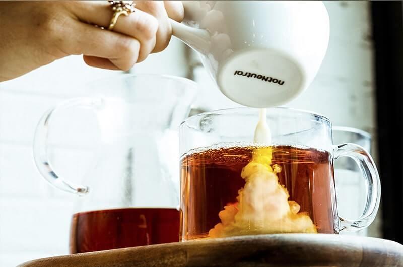 Наливает в чай молоко