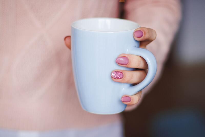 Белая чашка в женской руке