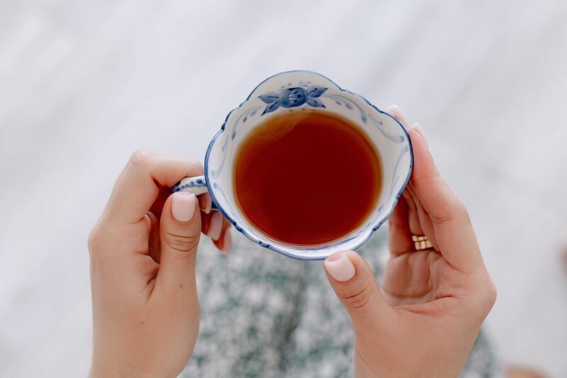Белая чашка чая в руках