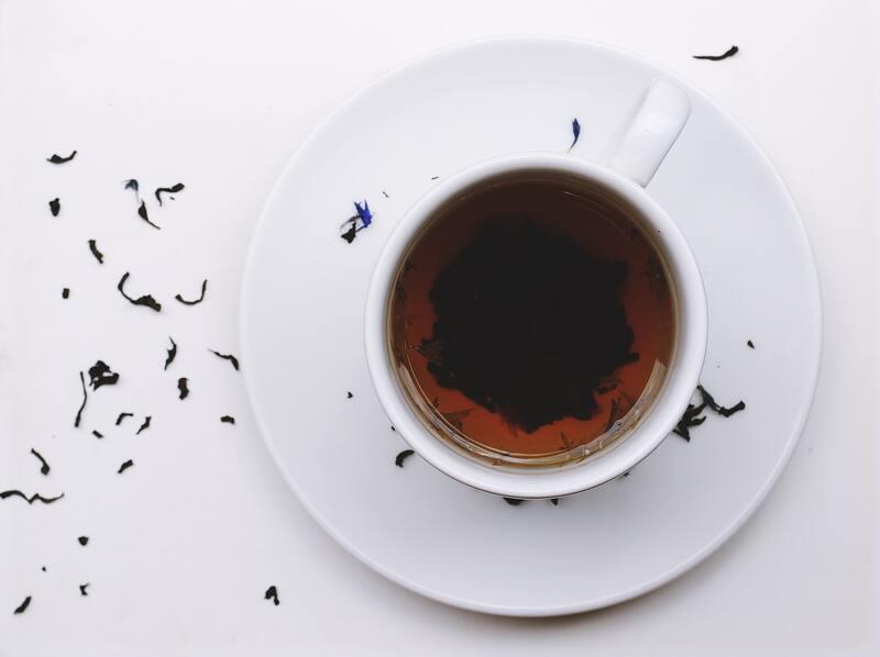 Кружка черного чая на белом фоне