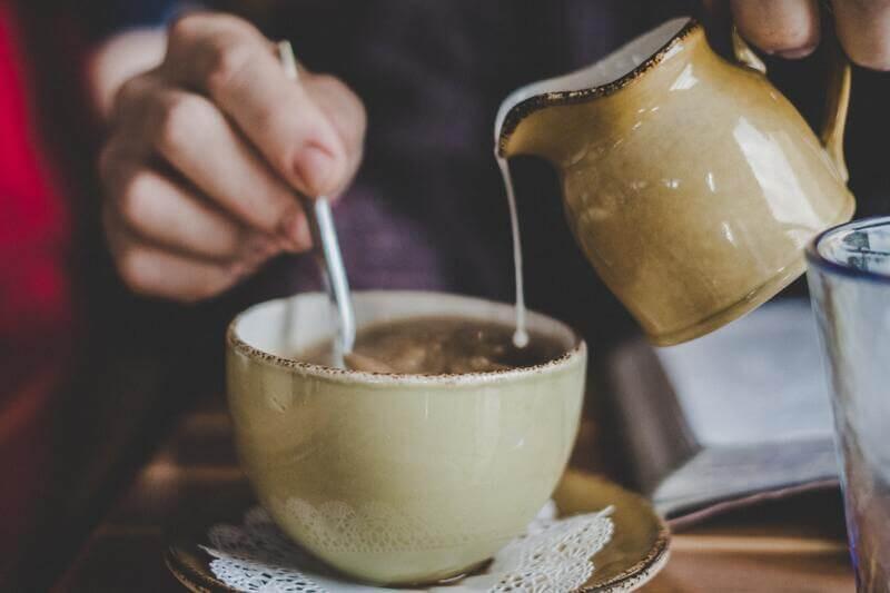 Размешивает чай с молоком
