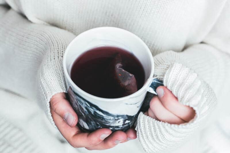 Чашка травяного чая в руках в свитере