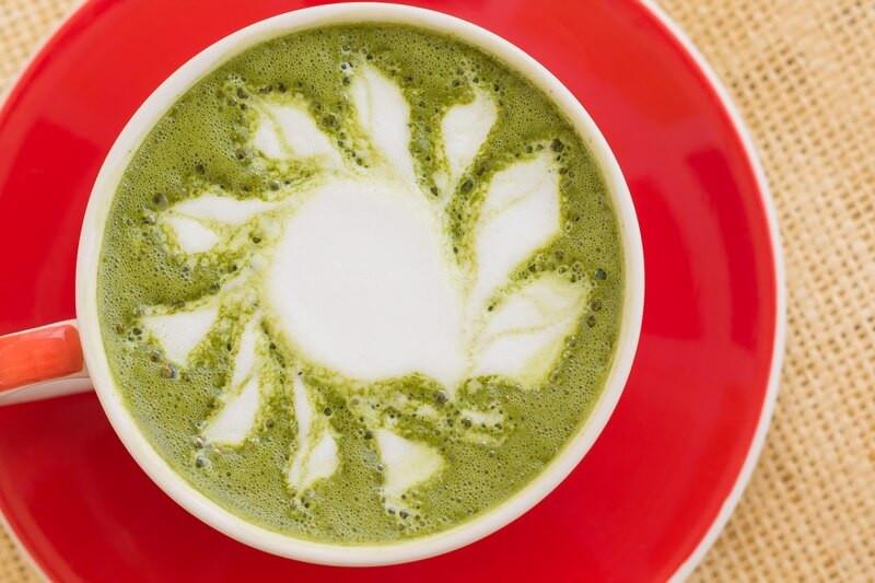 Зеленый чай с молоком в кружке на красной тарелке