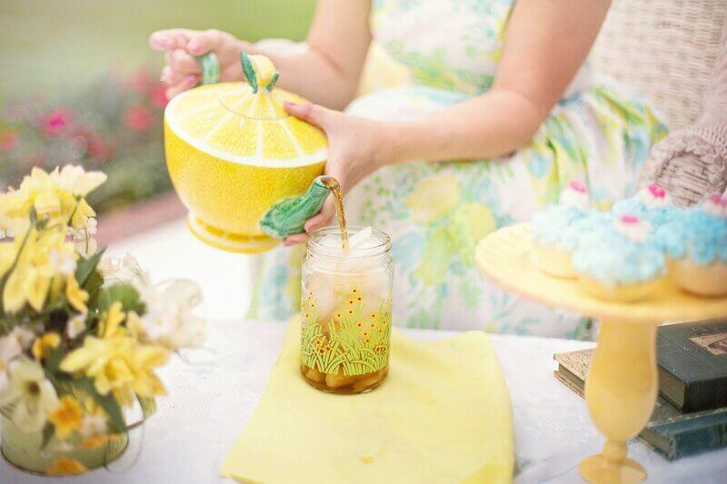 Женщина наливает чай в стакан со льдом