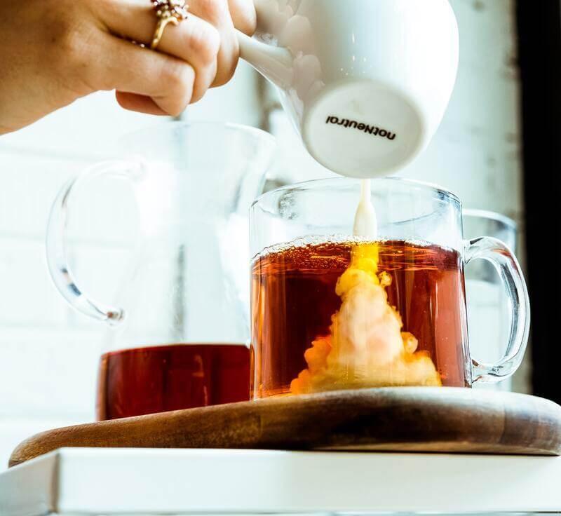 Наливает молоко в чай
