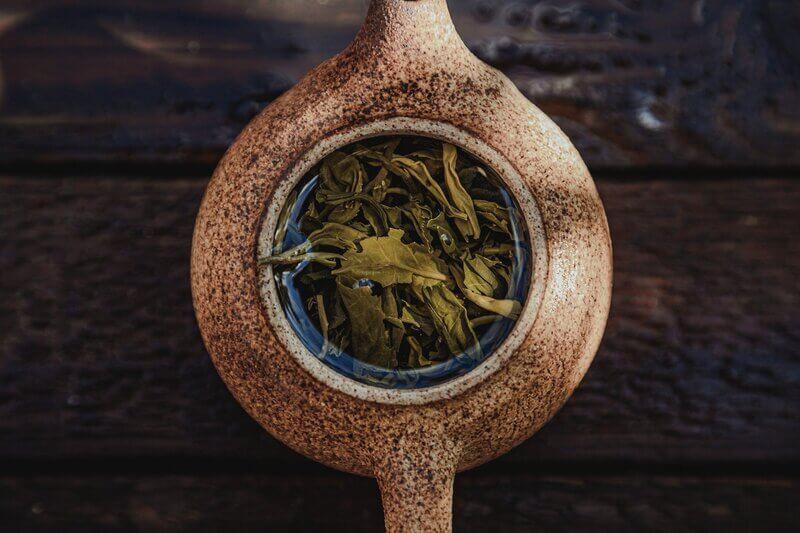 Глиняный коричневый чайник с заваркой