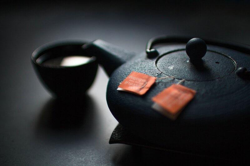 Черный чайник и пиала с чаем