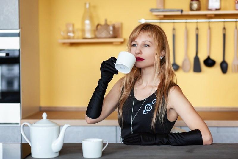 Девушка в черном пьет чай