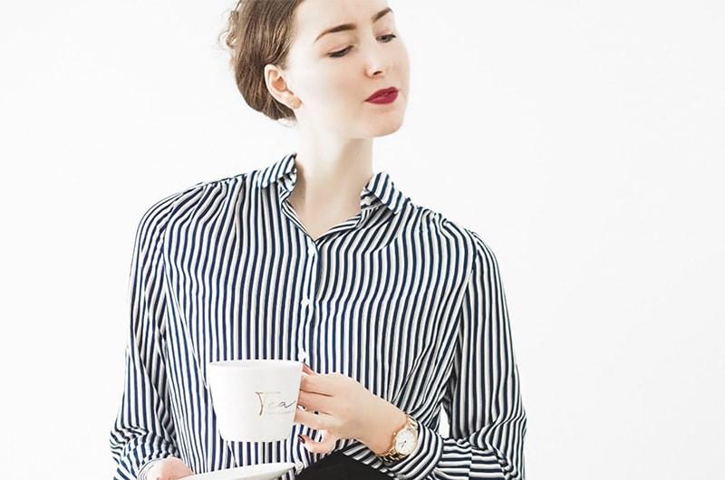 Девушка с чашкой в полосатой рубашке